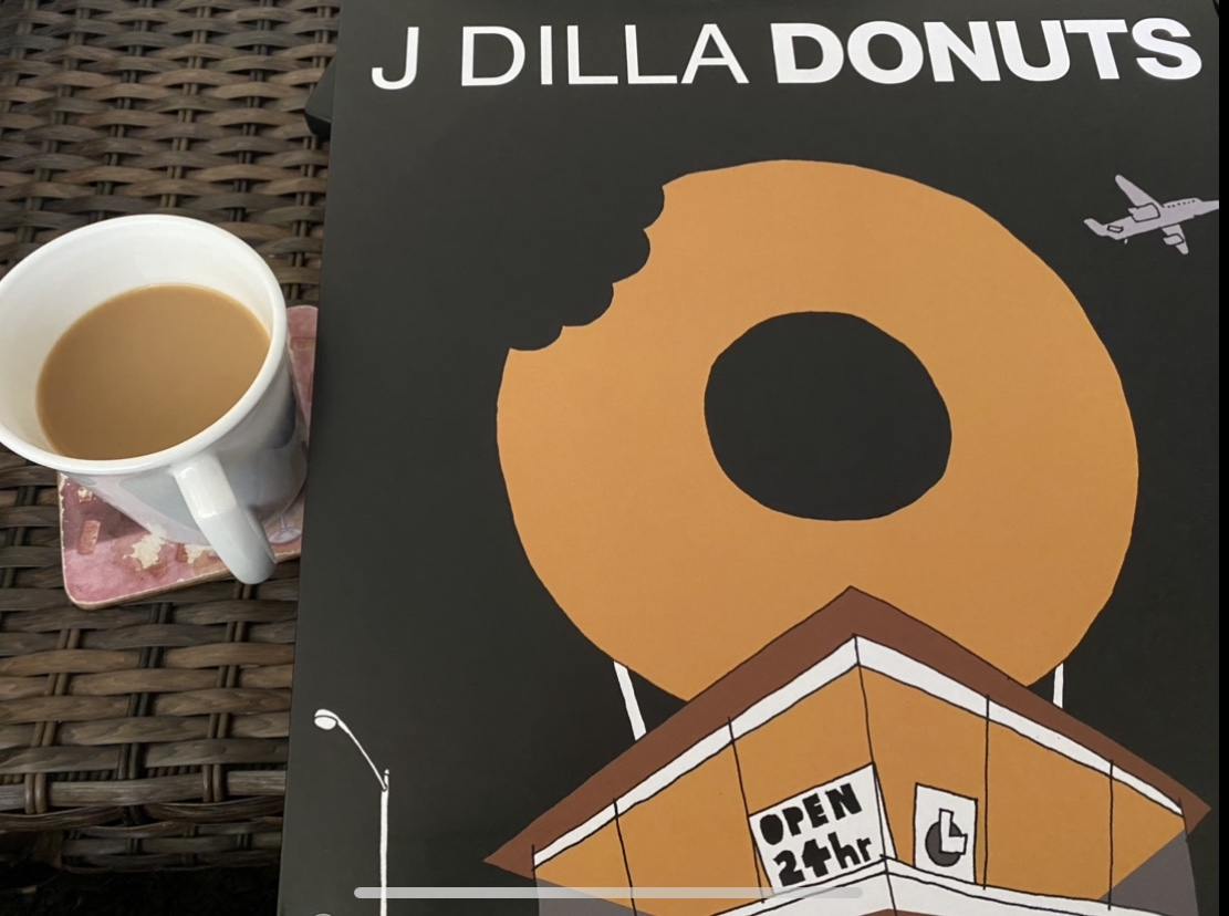 "Album cover of J Dilla's instrumental beats record, ""Donuts"" pictured next to a cup of coffee"